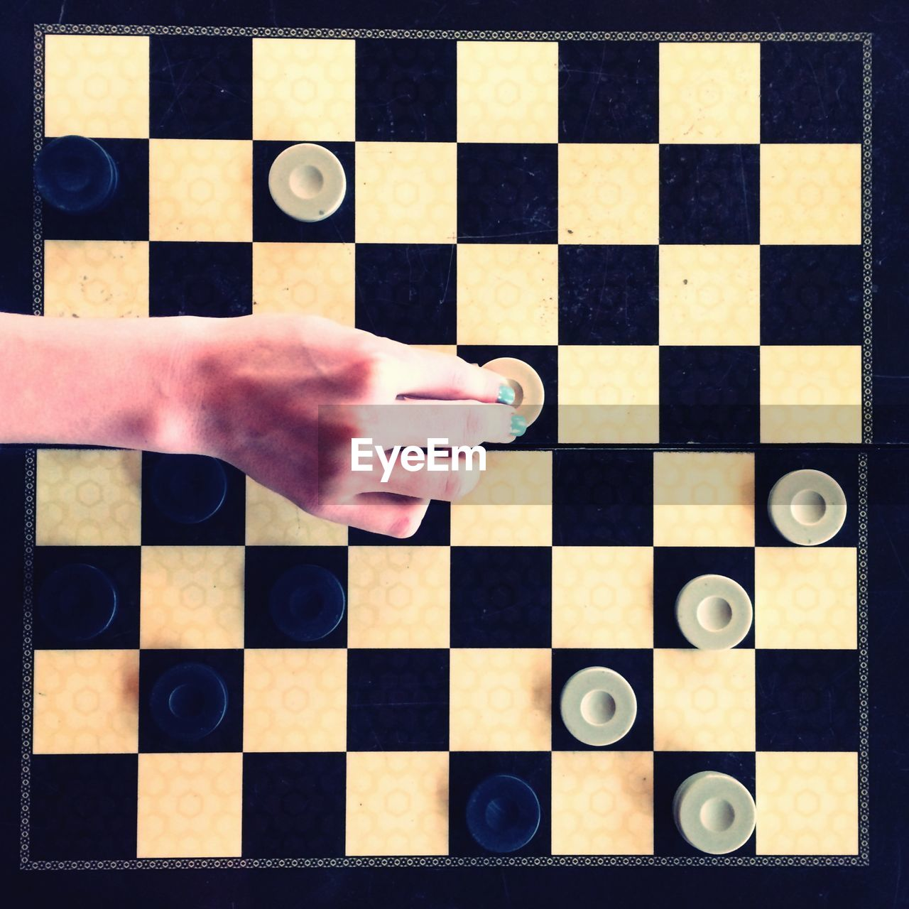 chess board, checked pattern, chess, leisure games, human body part, chess piece, human hand, strategy, high angle view, one person, indoors, competition, close-up, real people, one man only, day, people