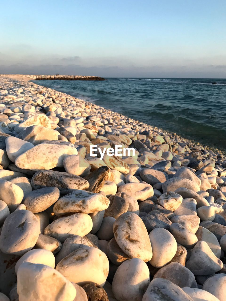pebble, sea, water, beach, shore, nature, pebble beach, tranquil scene, beauty in nature, outdoors, tranquility, scenics, no people, day, horizon over water, clear sky, sky, close-up