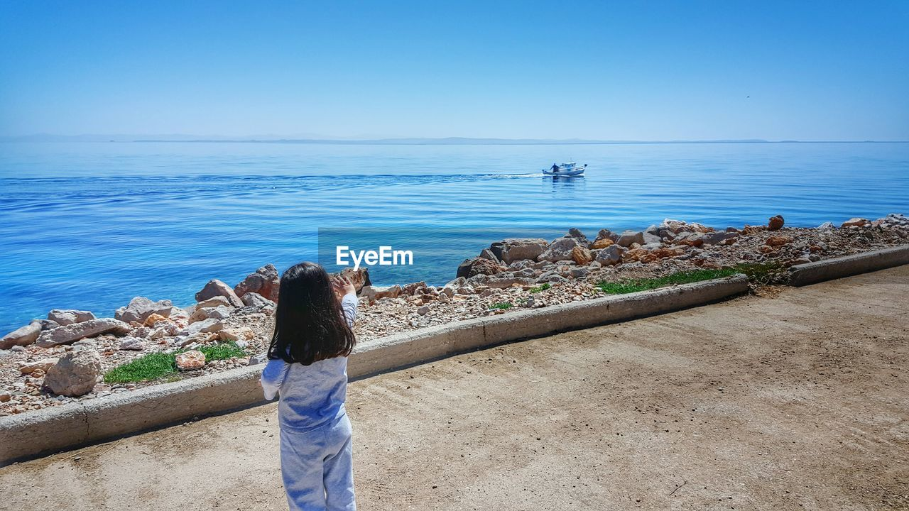 Rear View Of Little Girl Waving On Promenade By Sea Against Clear Sky