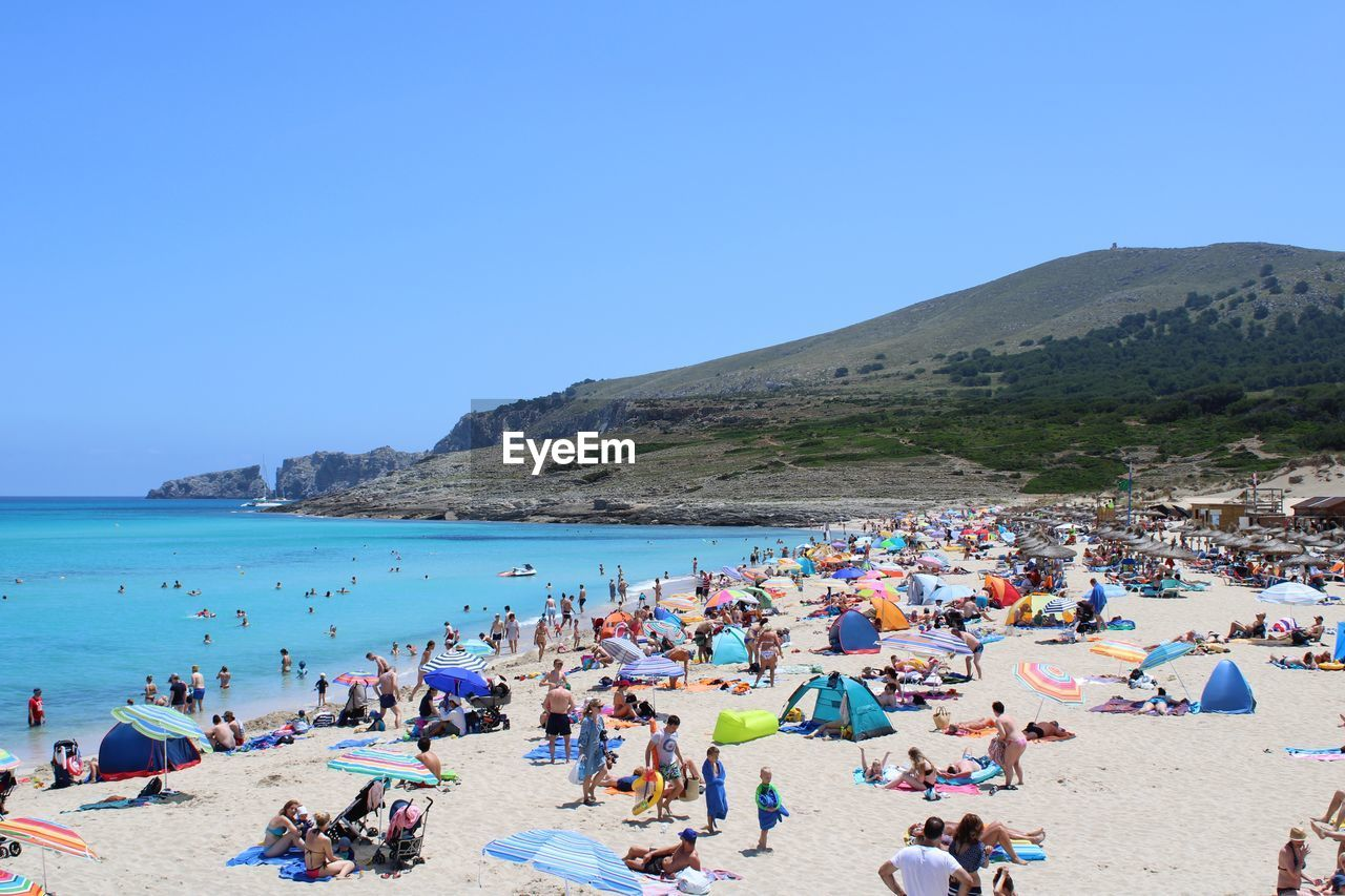 High angle view of people at beach against clear blue sky