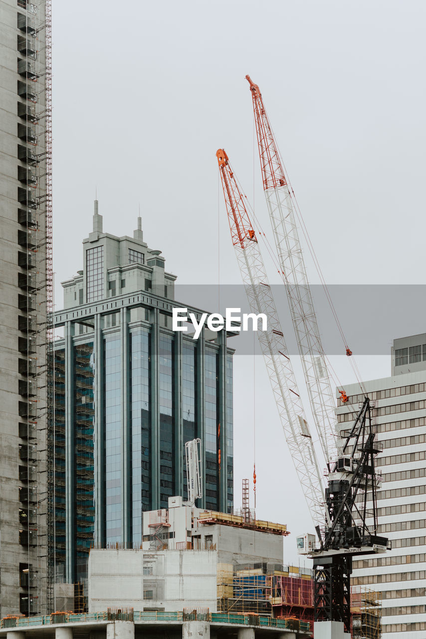 architecture, crane - construction machinery, built structure, building exterior, machinery, construction site, construction industry, development, industry, incomplete, sky, city, building, day, low angle view, tall - high, nature, construction machinery, no people, office building exterior, outdoors, construction equipment, skyscraper