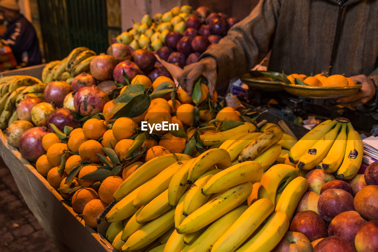 food, food and drink, healthy eating, market, fruit, retail, for sale, freshness, market stall, wellbeing, abundance, choice, large group of objects, banana, day, real people, business, variation, one person, small business, outdoors, orange, sale, retail display