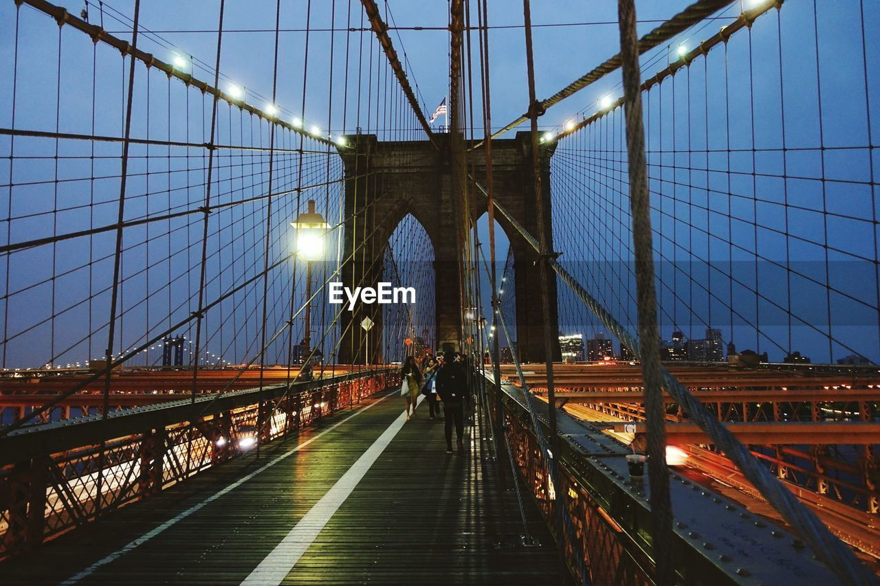 People On Illuminated Brooklyn Bridge Against Sky At Night