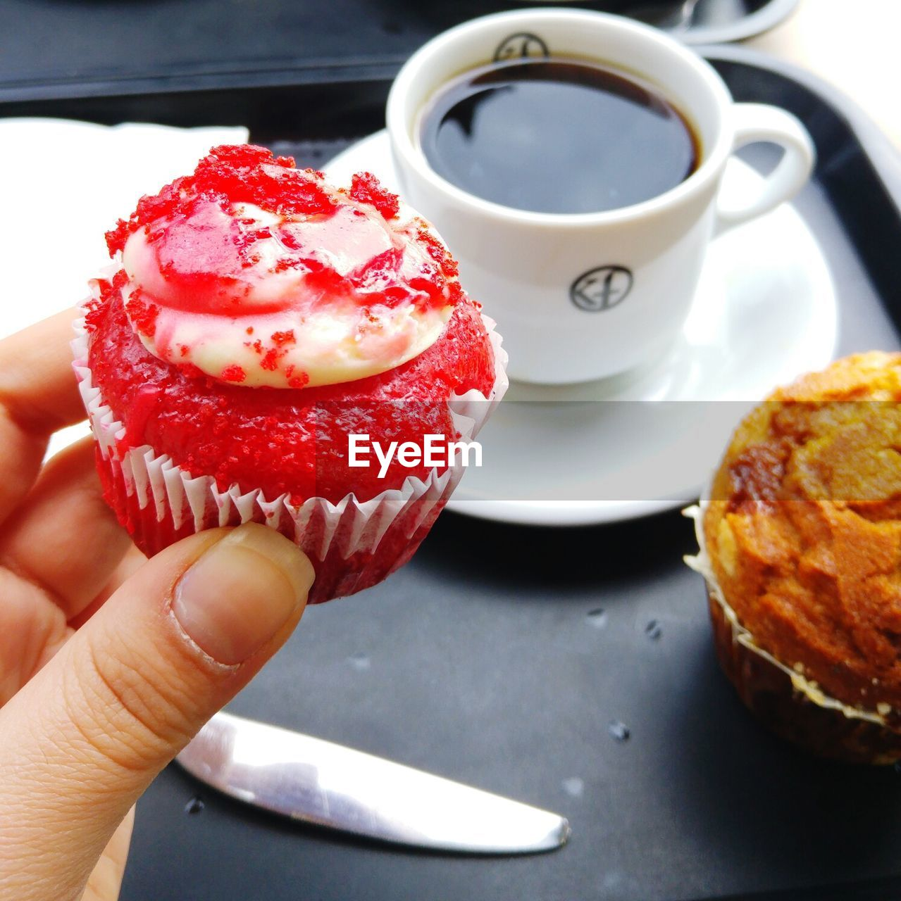 Cropped Image Of Person Holding Red Cupcake By Coffee In Tray