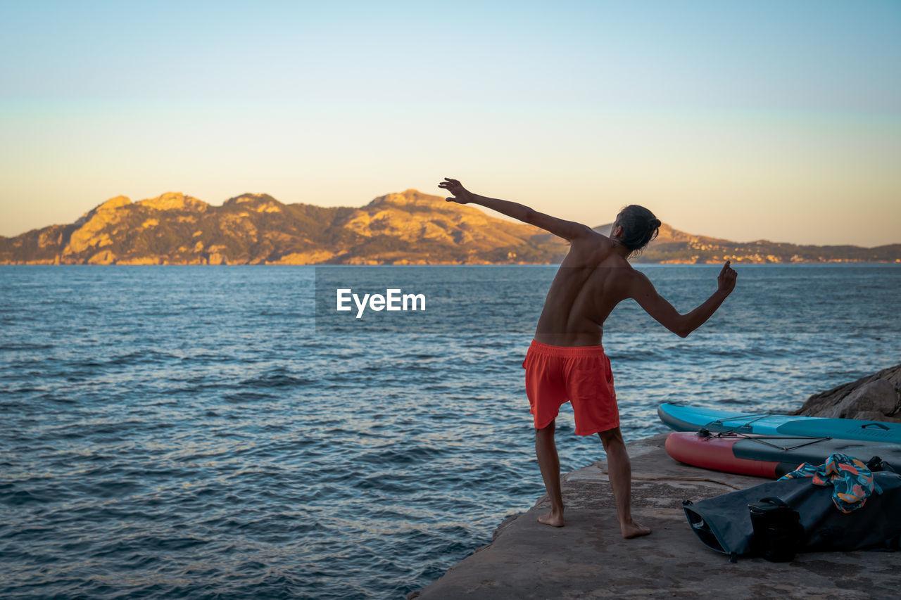 Rear view of shirtless man throwing rock to sea