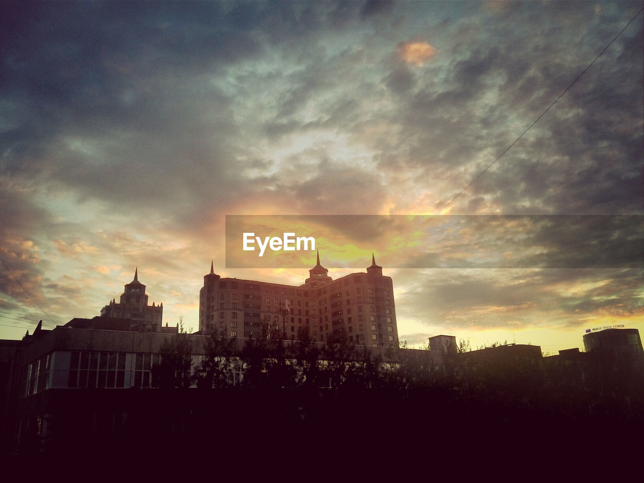 architecture, building exterior, built structure, sunset, sky, city, cloud - sky, silhouette, cloudy, cityscape, orange color, residential building, city life, dusk, cloud, building, residential structure, outdoors, residential district, dramatic sky