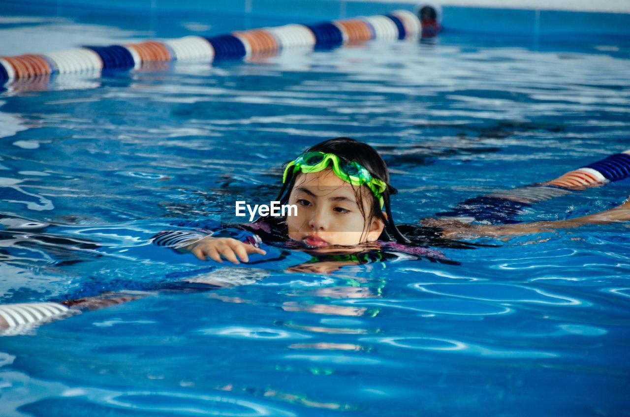 Portrait of boy swimming in pool