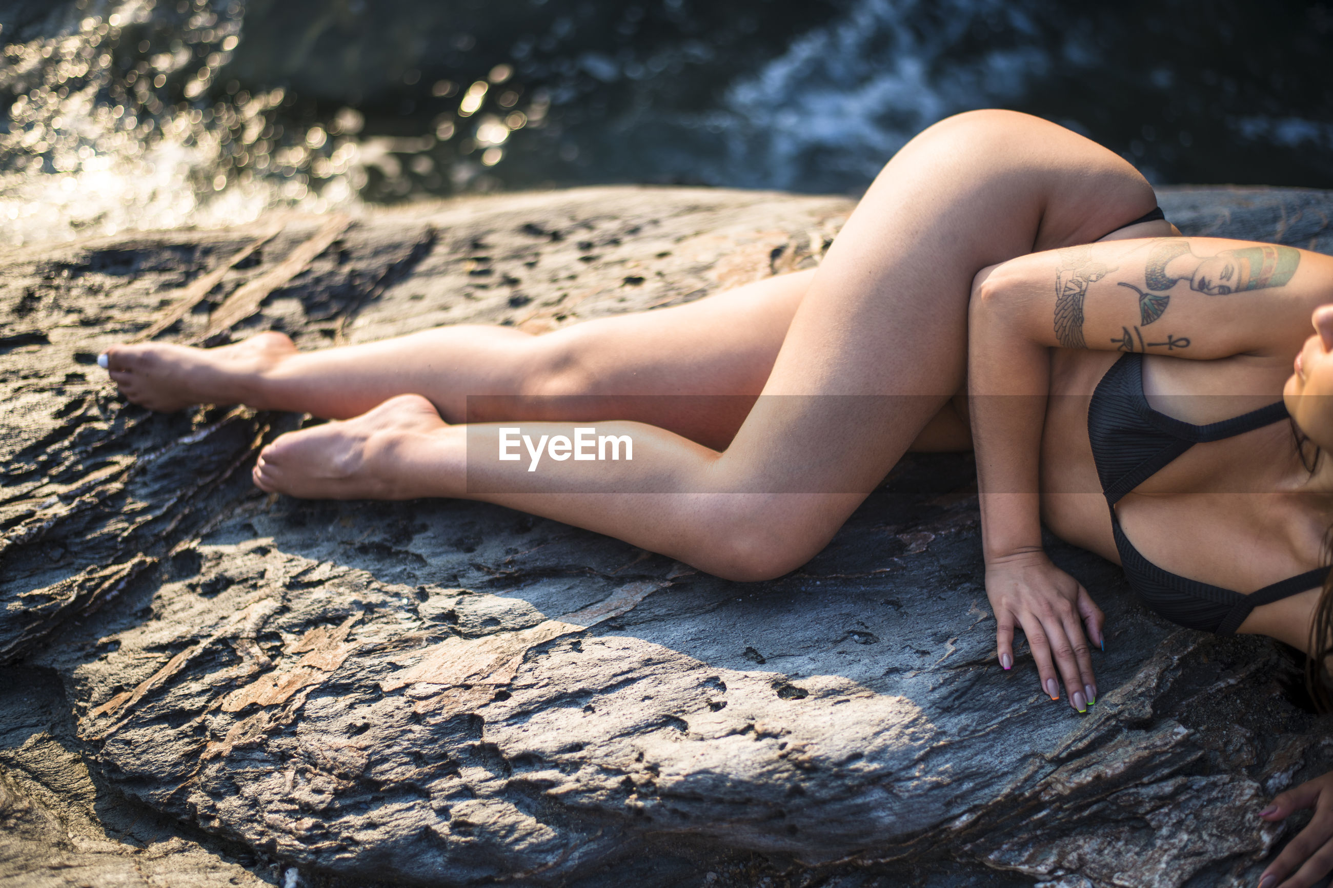 MIDSECTION OF WOMAN LYING ON SHORE