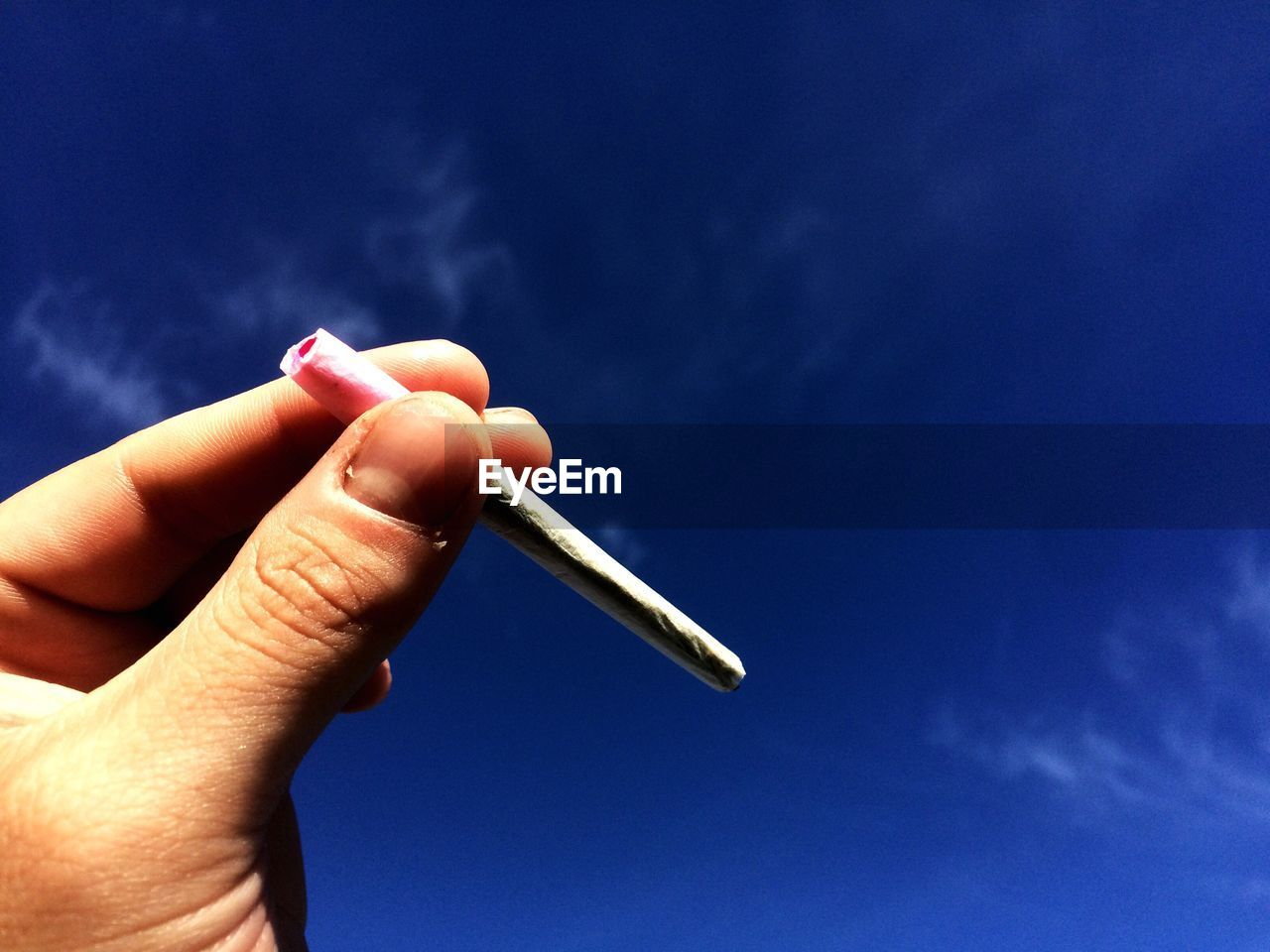Cropped Image Of Hand Holding Marijuana Joint Against Sky