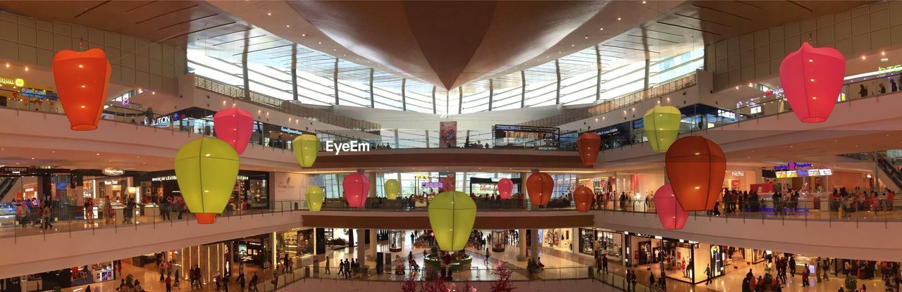 indoors, large group of people, ceiling, lifestyles, retail, women, built structure, architecture, leisure activity, real people, architectural column, modern, illuminated, men, crowd, day, people