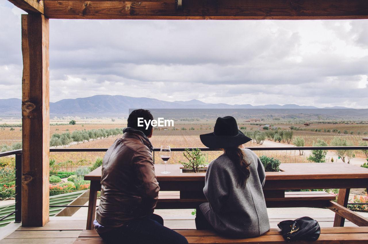 Rear View Of Friends Sitting On Bench In Gazebo Against Landscape
