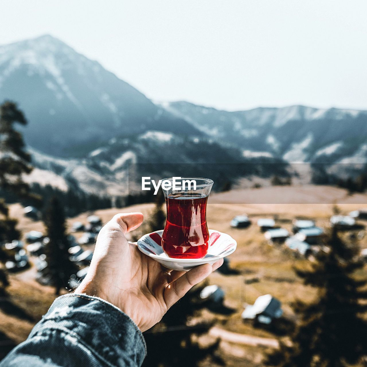 human hand, mountain, drink, hand, one person, human body part, refreshment, holding, mountain range, food and drink, day, leisure activity, lifestyles, focus on foreground, glass, cold temperature, real people, nature, scenics - nature, personal perspective, body part, outdoors, snowcapped mountain, finger