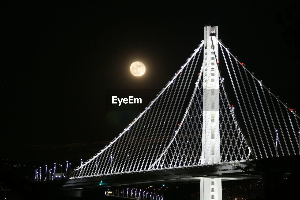 Low angle view of bay bridge against moon in sky at night