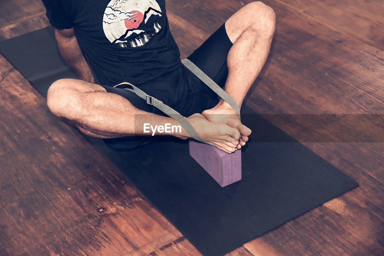 Low Section Of Man Exercising On Hardwood Floor