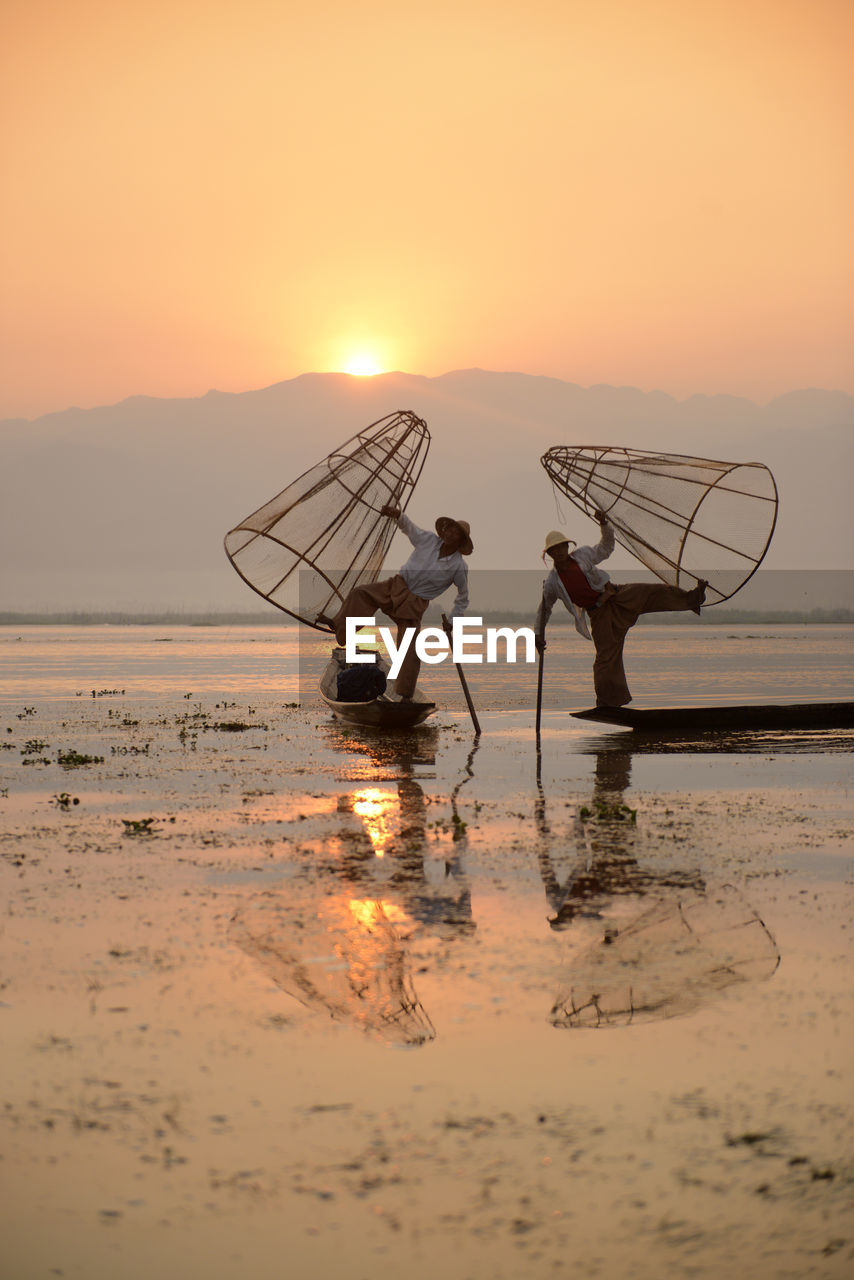 sunset, orange color, nature, occupation, fishing net, fisherman, water, reflection, men, nautical vessel, sky, mode of transport, waterfront, beauty in nature, transportation, scenics, outdoors, silhouette, real people, lake, full length, day