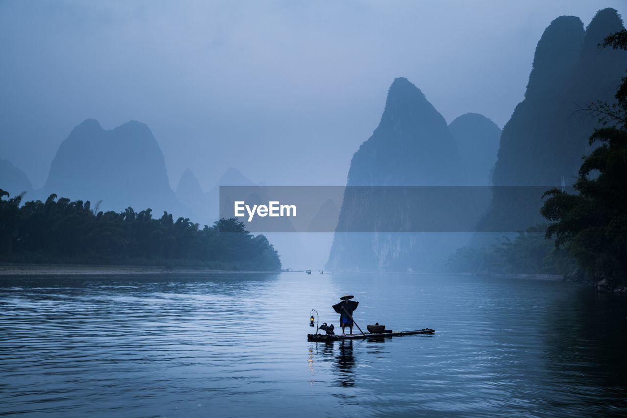 Senior man standing on wooden raft in lake against sky during foggy weather