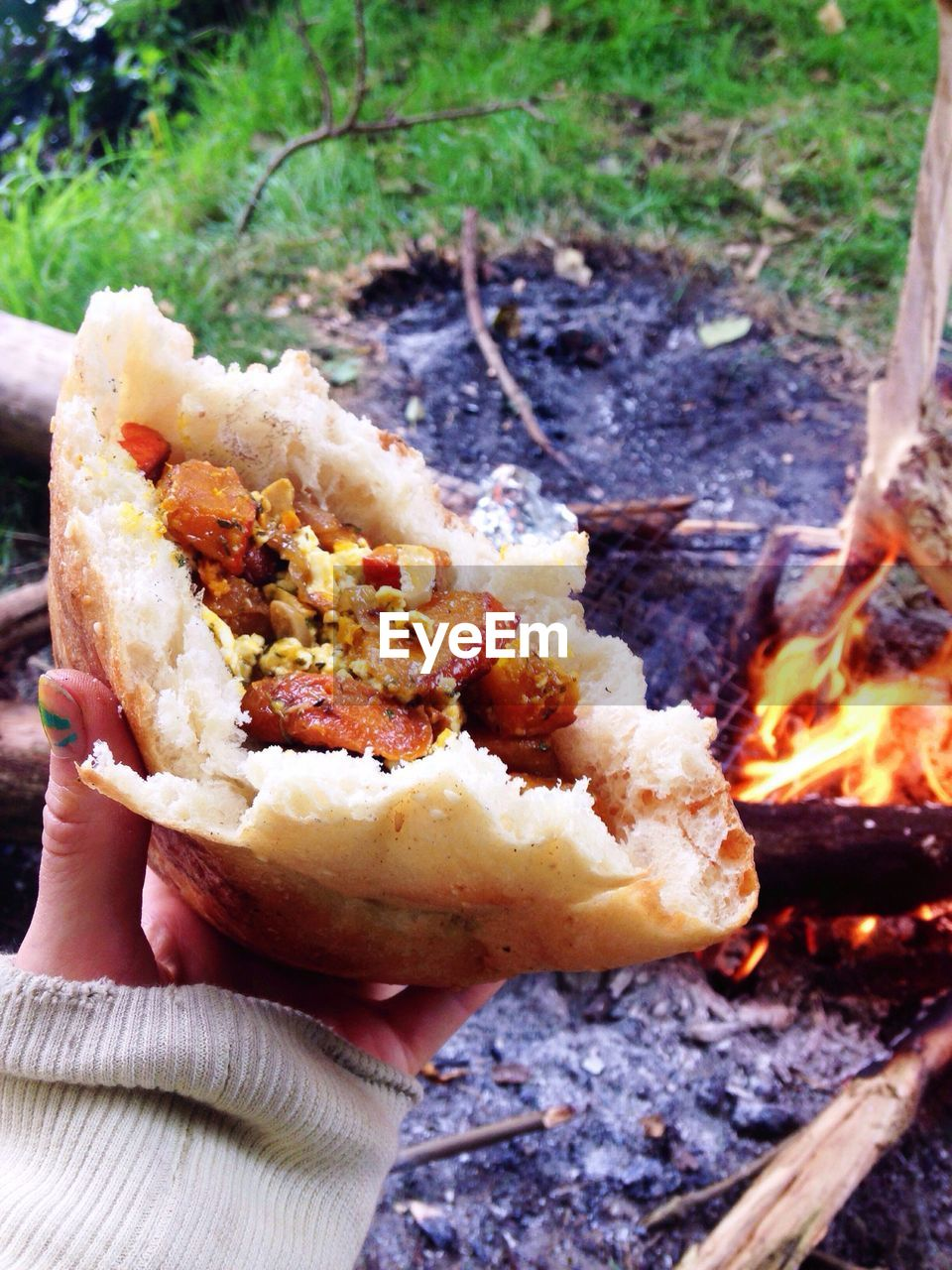 Close-Up Of Cropped Woman Hand Holding Food By Campfire
