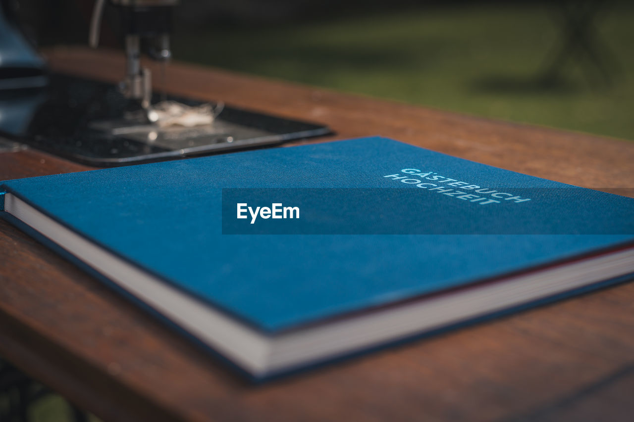 selective focus, blue, close-up, table, no people, indoors, wood - material, text, preparation, day, still life, art and craft, communication, leisure activity, focus on foreground, creativity, publication, design