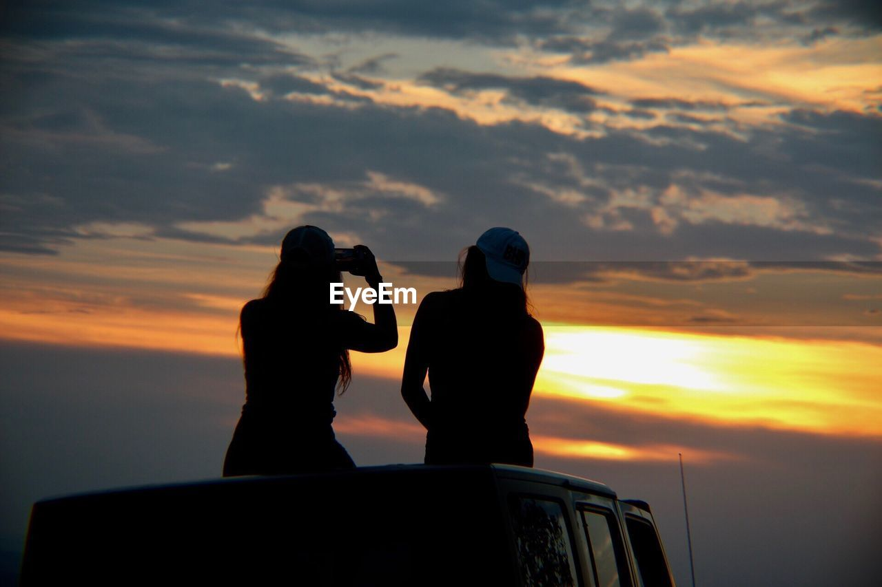 sunset, sky, cloud - sky, two people, mode of transportation, men, photographing, orange color, beauty in nature, photography themes, transportation, real people, nature, leisure activity, technology, activity, scenics - nature, lifestyles, silhouette, women, outdoors, couple - relationship