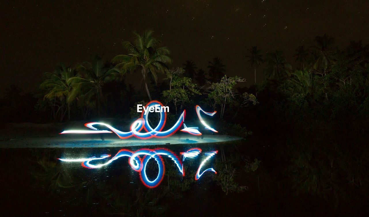 Light painting on lakeshore at night
