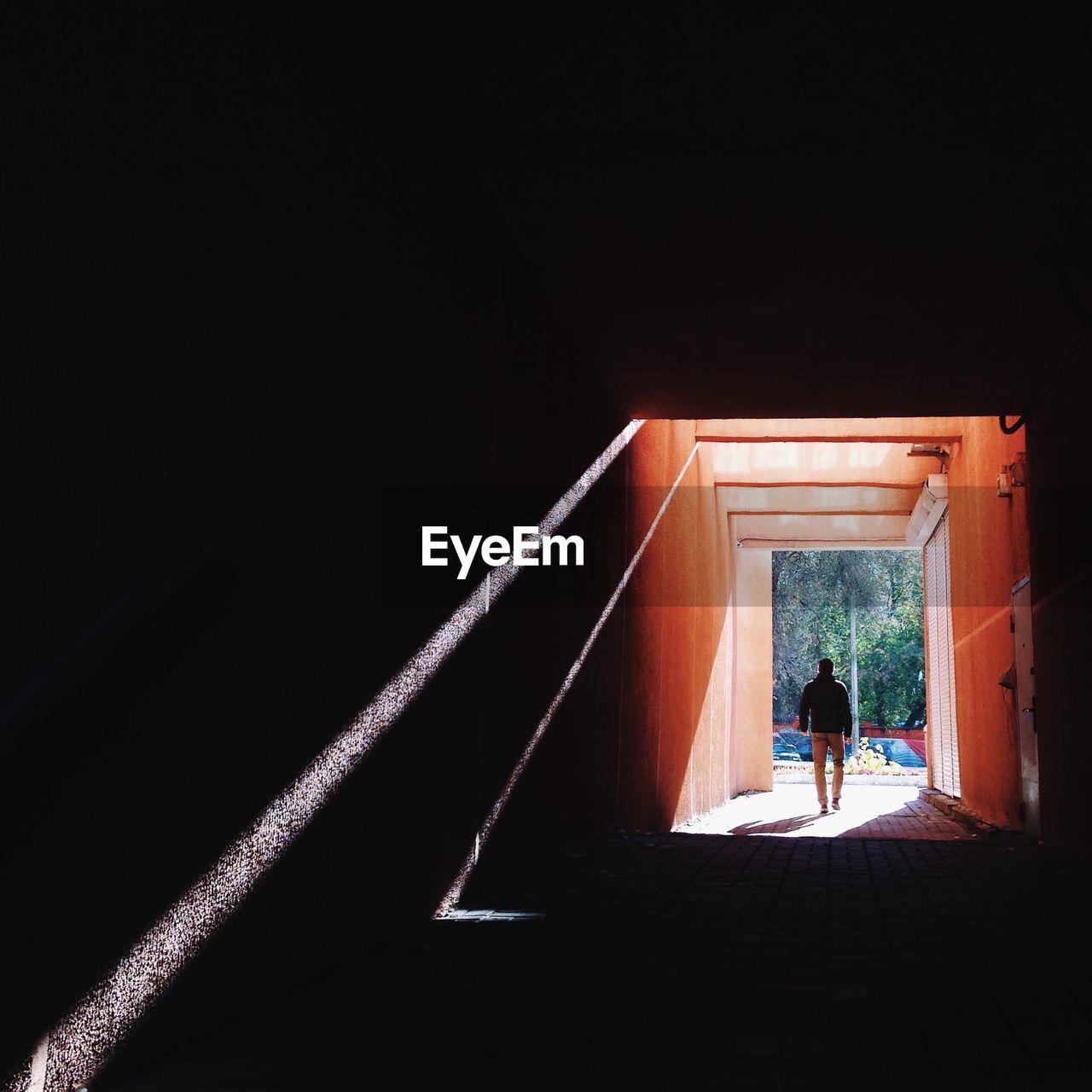 Rear View Of Man Waling Through Corridor