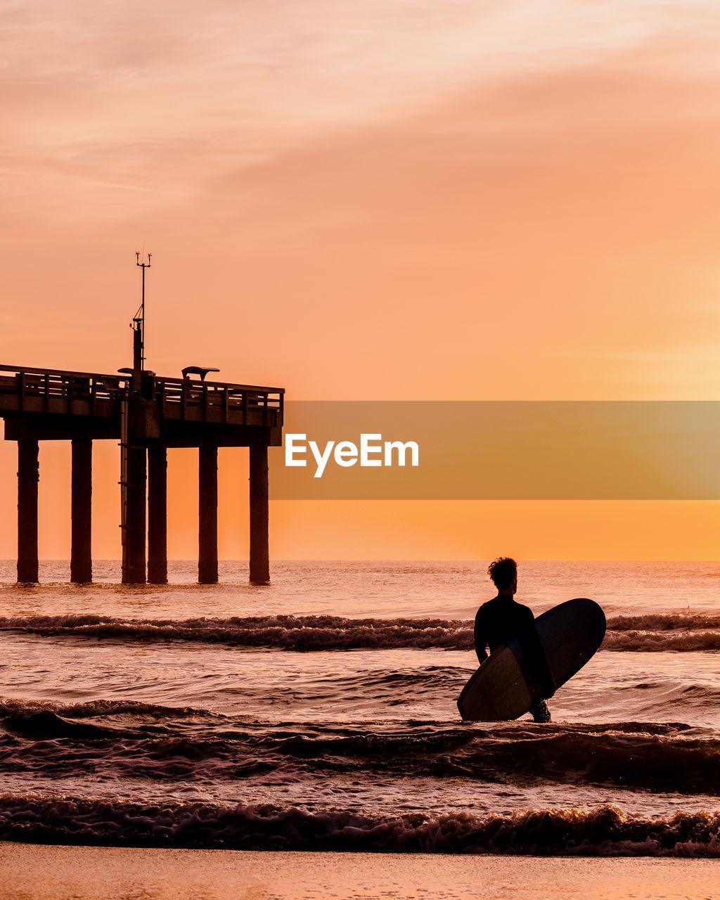 SILHOUETTE MAN ON BEACH AGAINST ORANGE SKY