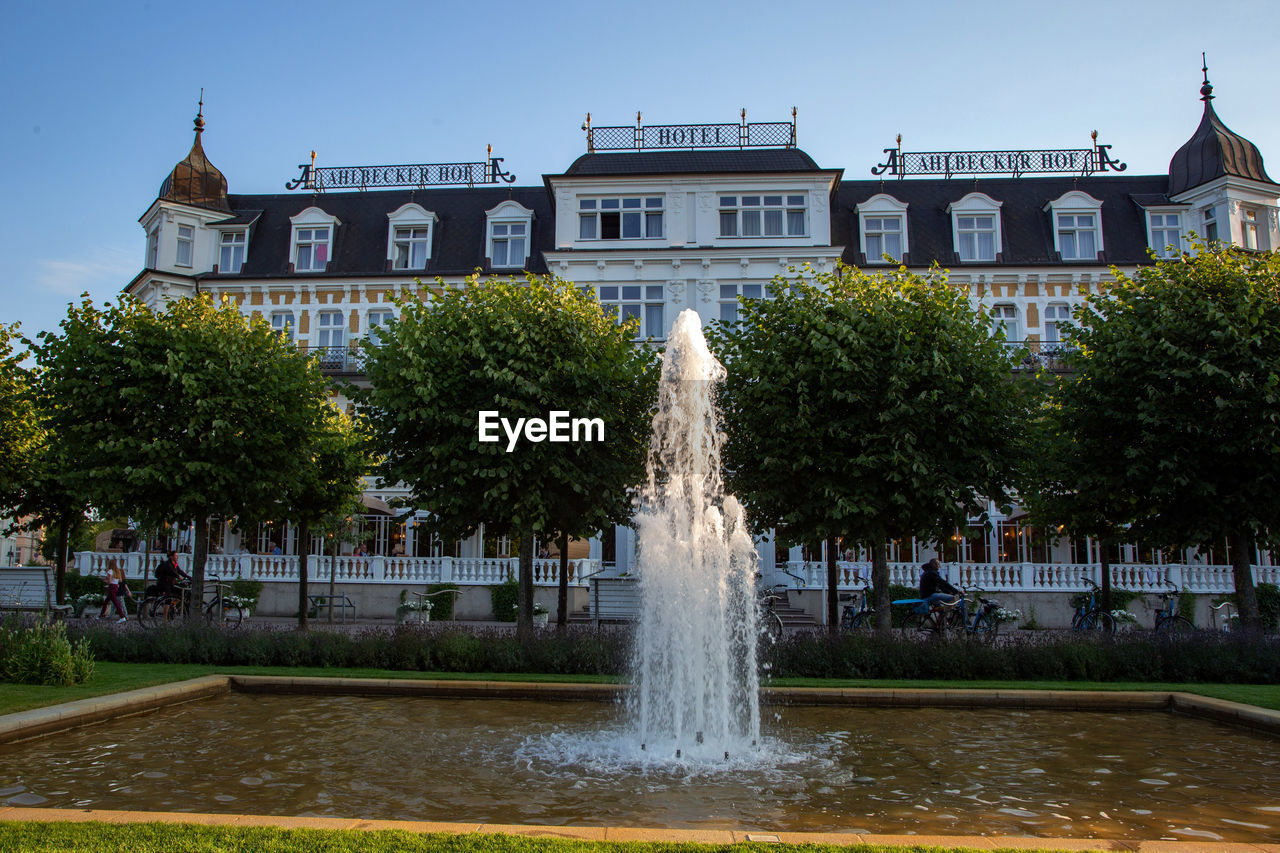 architecture, water, built structure, building exterior, fountain, plant, tree, nature, spraying, building, motion, sky, city, waterfront, travel destinations, day, long exposure, no people, outdoors, flowing water
