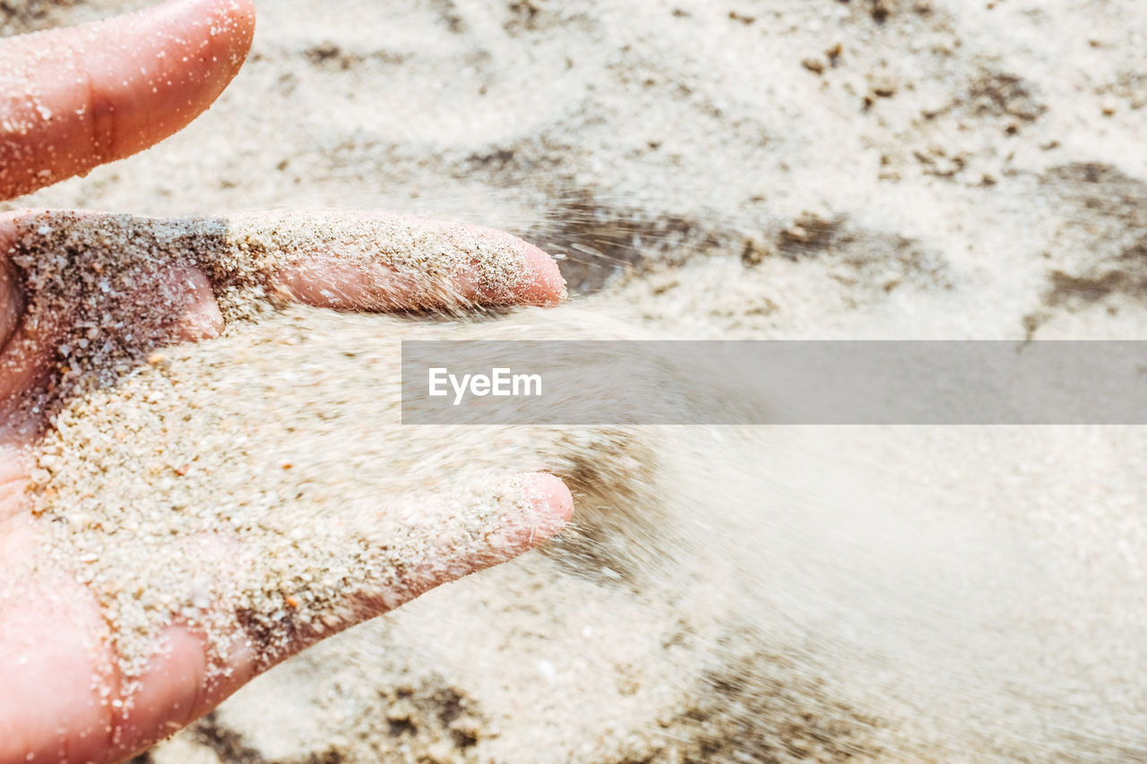 Close-up of hand holding sand at beach