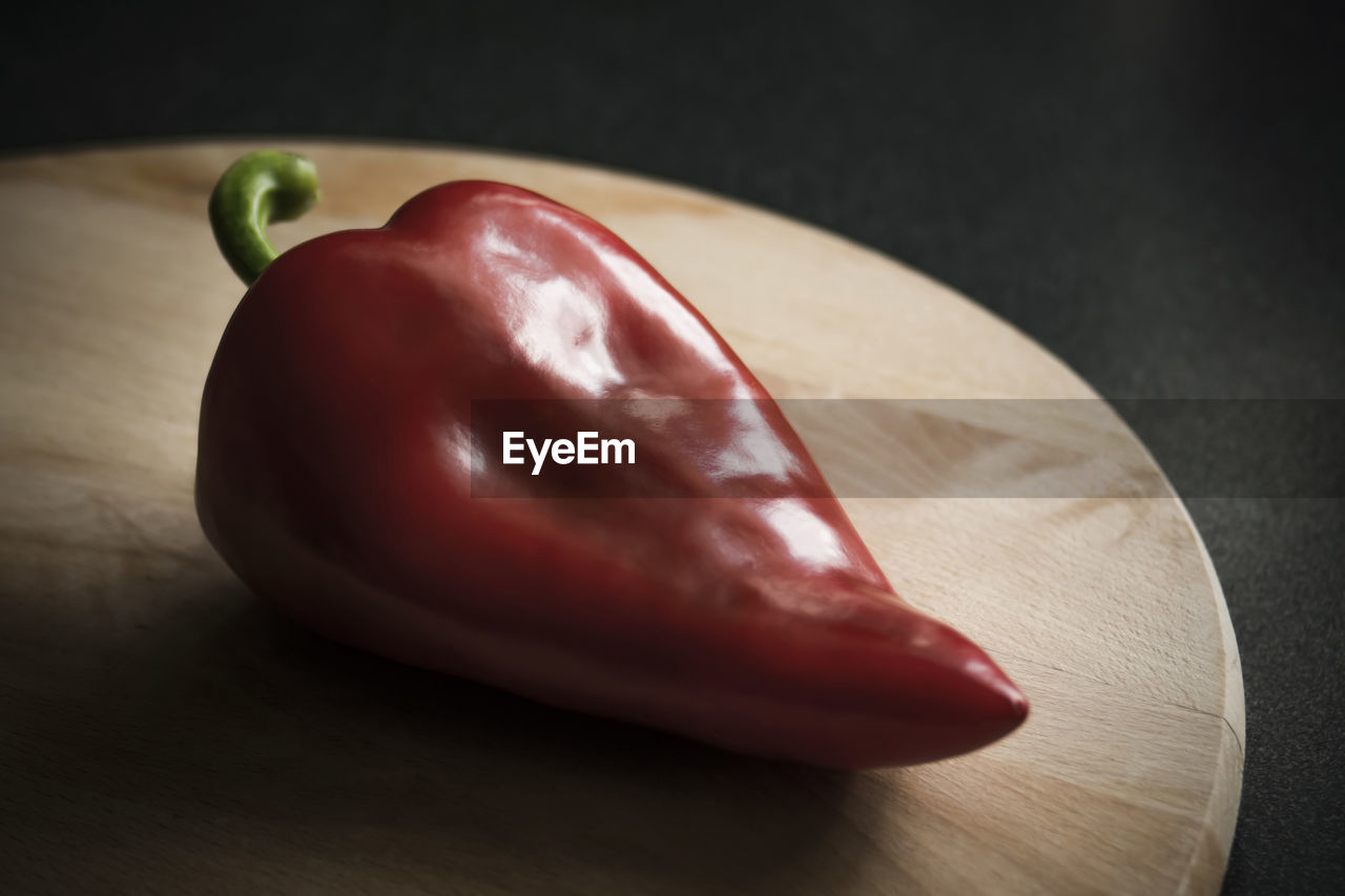 red, food, food and drink, freshness, indoors, healthy eating, pepper, close-up, table, wellbeing, still life, vegetable, no people, fruit, bell pepper, focus on foreground, single object, wood - material, red bell pepper, spice