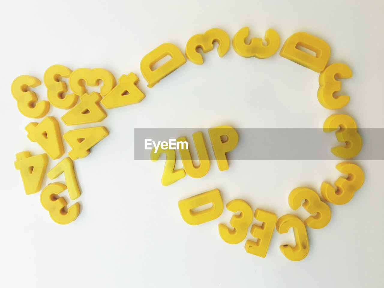 white background, indoors, western script, studio shot, text, still life, letter, communication, close-up, capital letter, food and drink, food, alphabet, no people, large group of objects, high angle view, yellow, shape, arrangement, cookie, snack