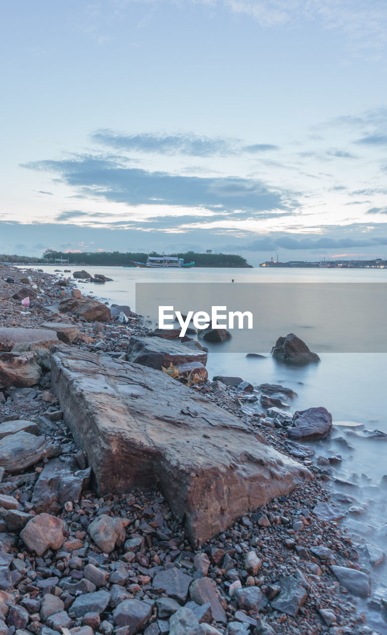 water, sky, scenics - nature, tranquility, sea, tranquil scene, cloud - sky, rock, nature, beauty in nature, solid, no people, beach, land, day, rock - object, non-urban scene, outdoors, stone, pebble, rocky coastline
