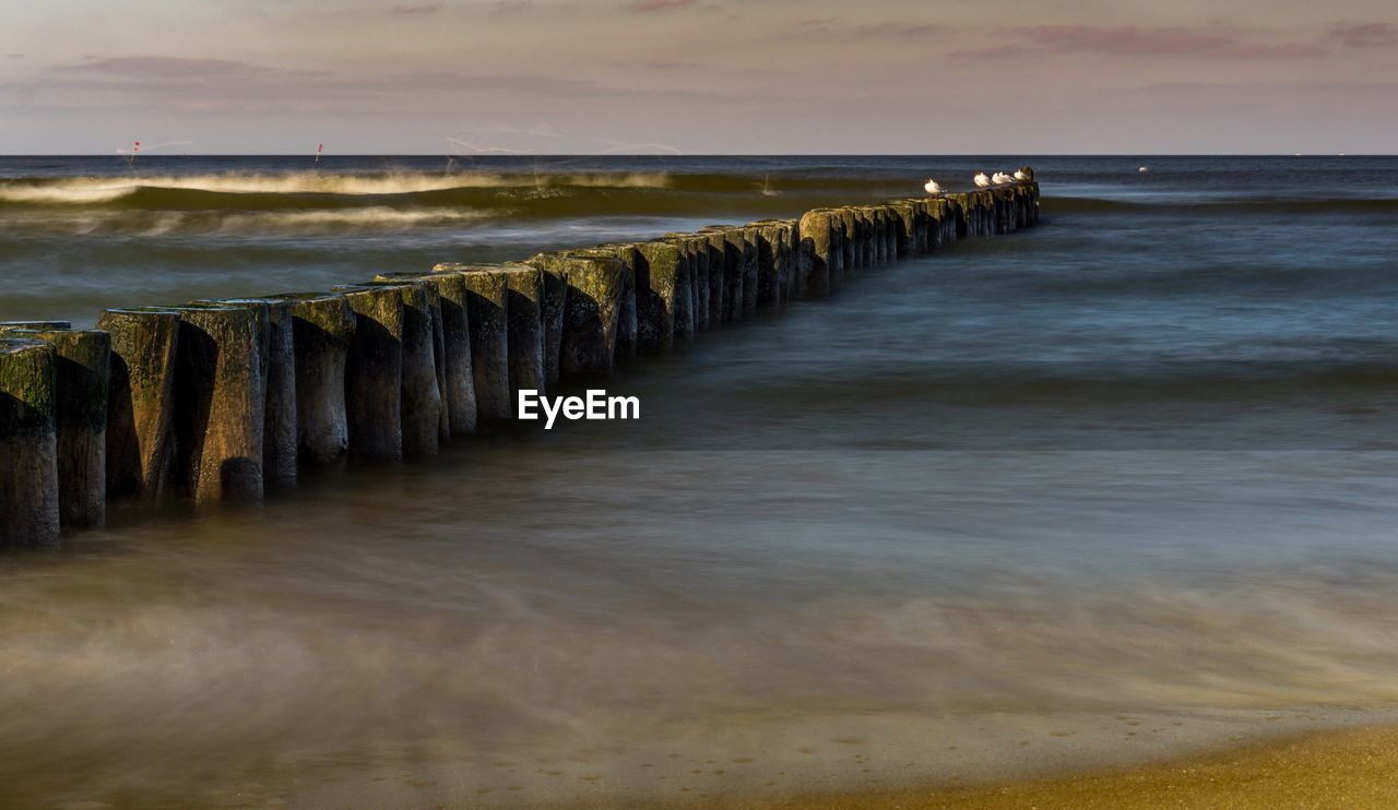 water, sea, sky, scenics - nature, beach, horizon, land, beauty in nature, horizon over water, tranquility, tranquil scene, nature, motion, no people, cloud - sky, wave, non-urban scene, sunset, wood - material, post, wooden post, outdoors, groyne