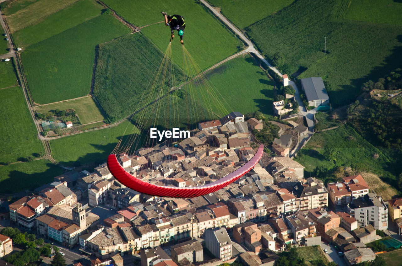 High Angle View Of Man Paragliding Over Townscape
