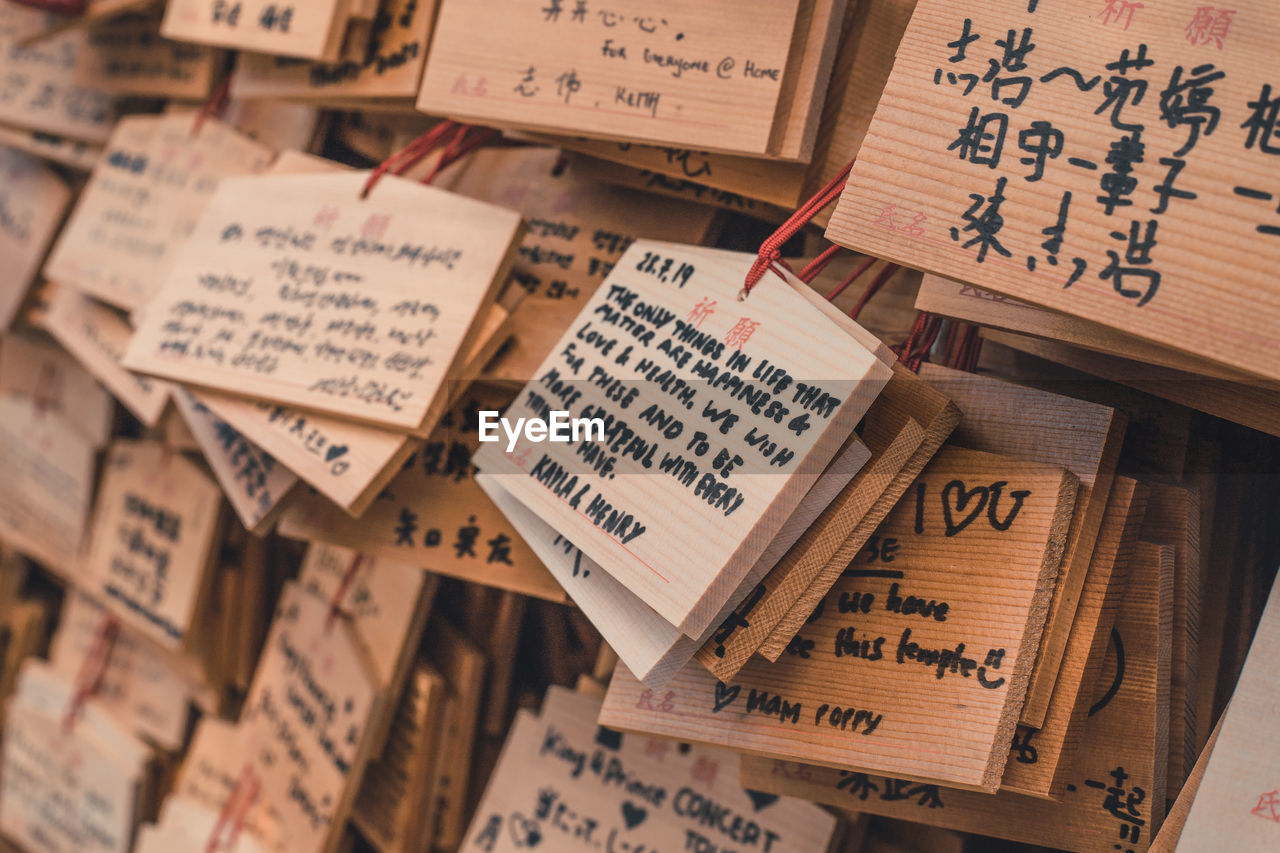 text, wood - material, no people, communication, large group of objects, indoors, non-western script, close-up, selective focus, script, abundance, full frame, still life, backgrounds, high angle view, paper, variation, choice, musical note, publication