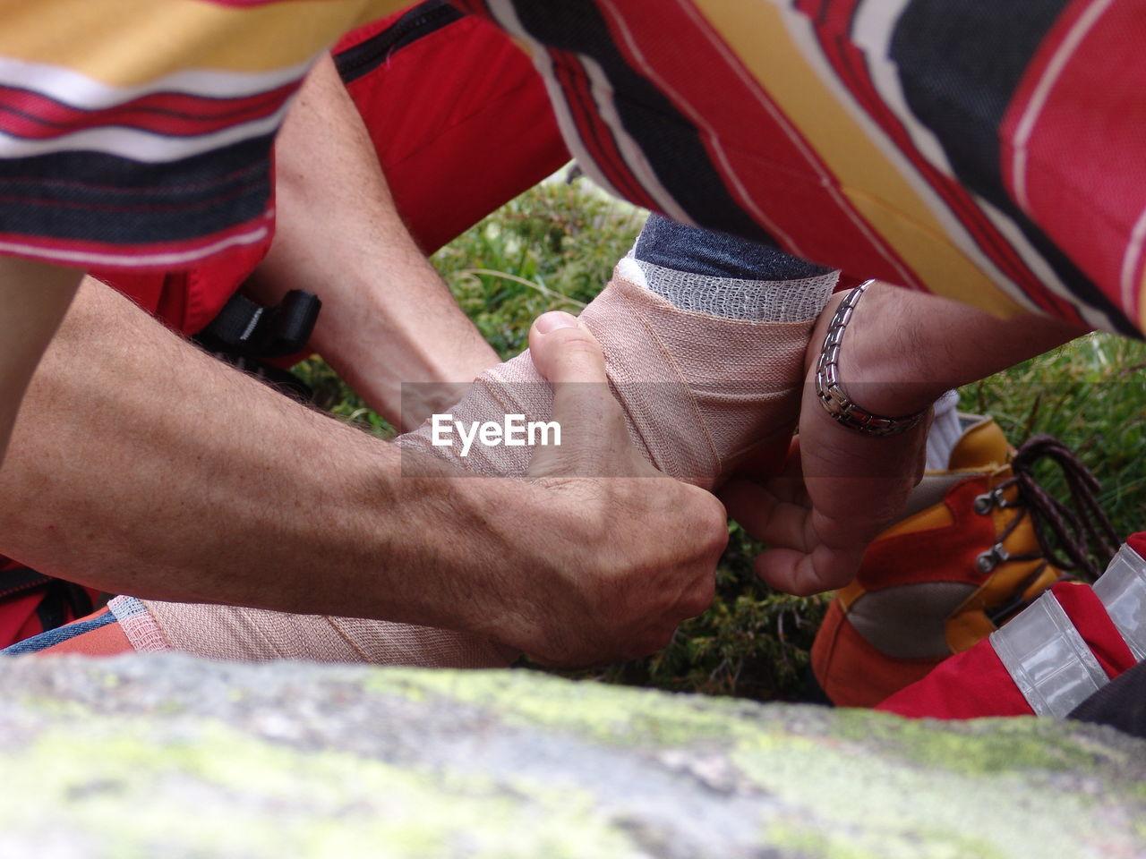 Hands tying bandage on man leg