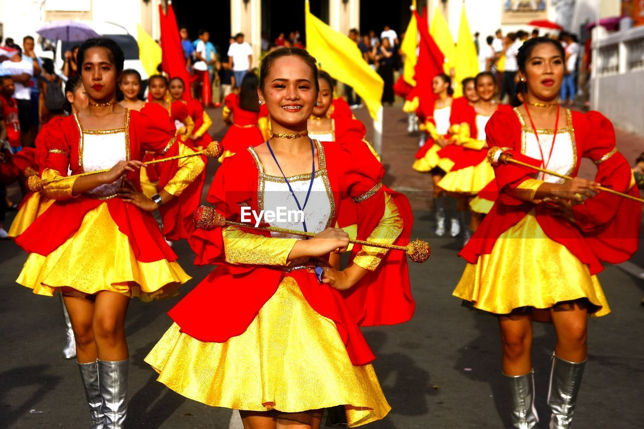 group of people, arts culture and entertainment, real people, women, traditional clothing, clothing, performance, smiling, celebration, leisure activity, dancing, focus on foreground, happiness, people, front view, adult, city, day, outdoors, traditional dancing, carnival - celebration event