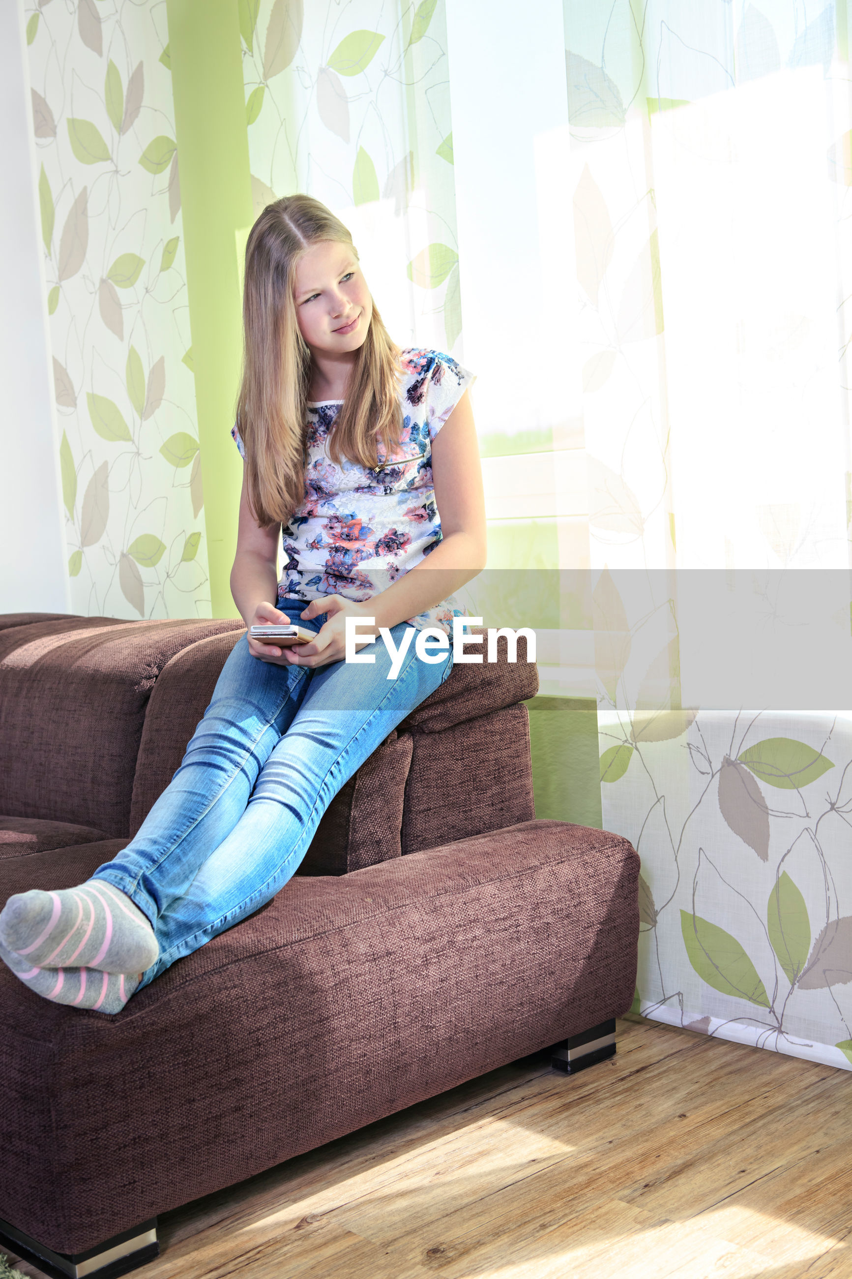 Young woman using smart phone while sitting on sofa at home