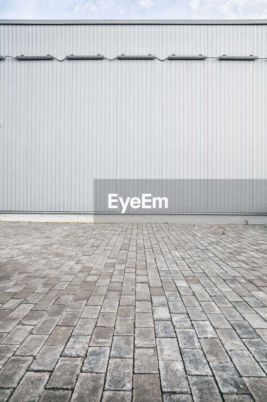 architecture, footpath, no people, built structure, pattern, wall - building feature, metal, day, iron, street, corrugated iron, flooring, building exterior, industry, outdoors, city, stone, textured, copy space, absence, tiled floor, paving stone, corrugated
