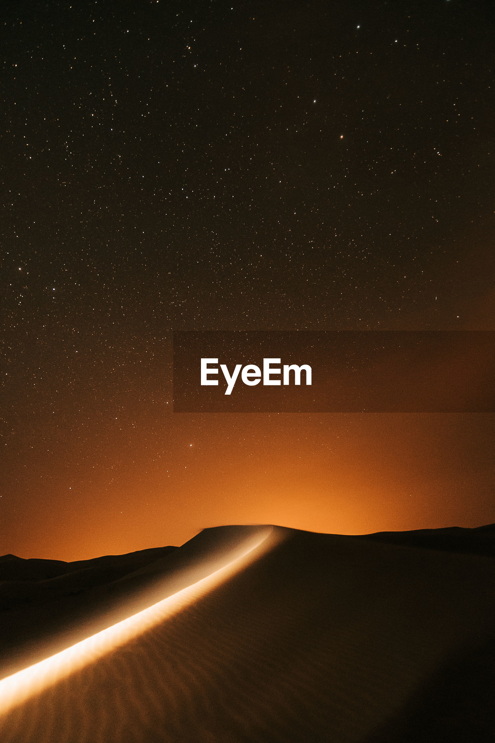 Scenic view of landscape against sky at night in the desert full of stars