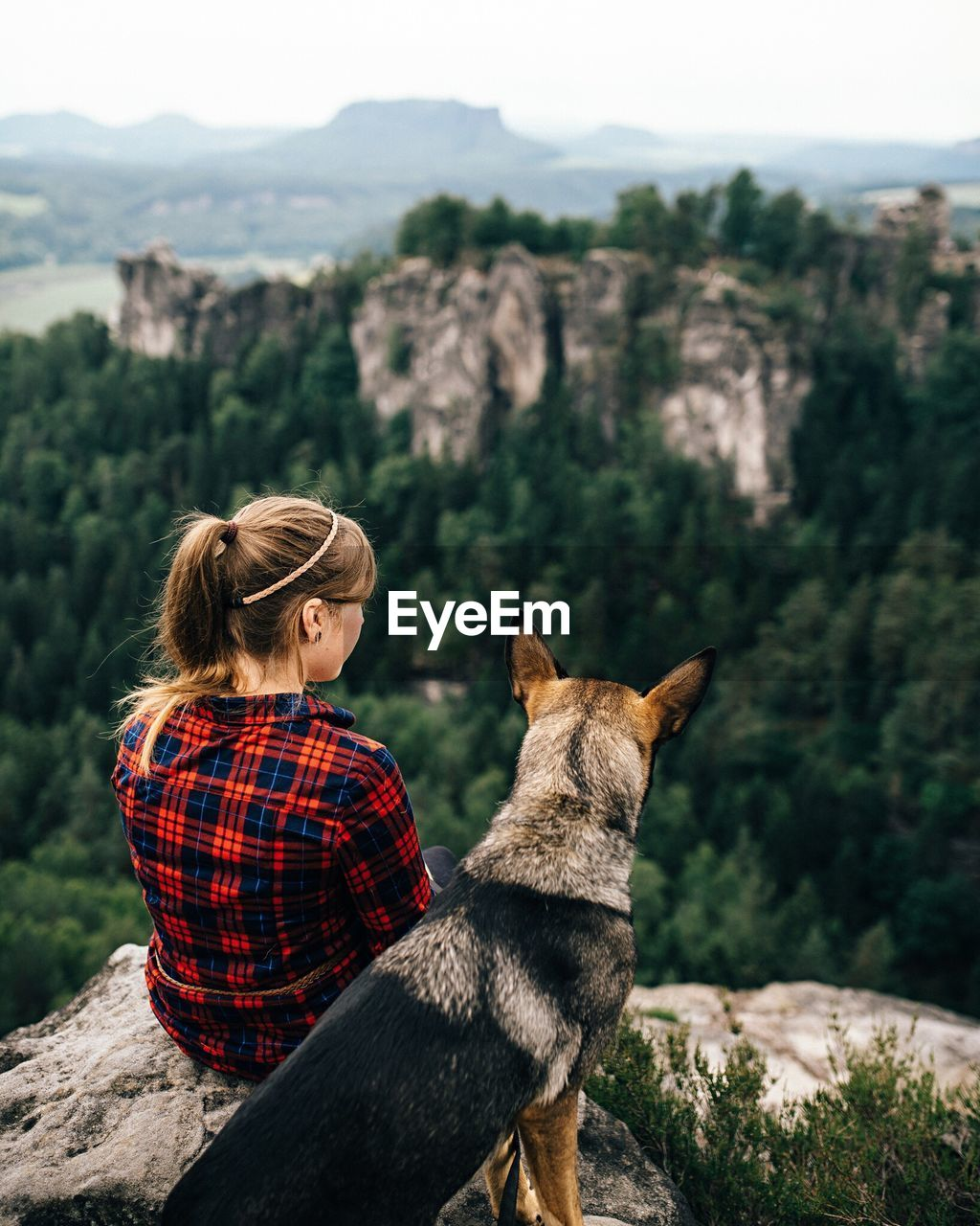 Rear View Of Woman Sitting With Dog At Mountain Peak
