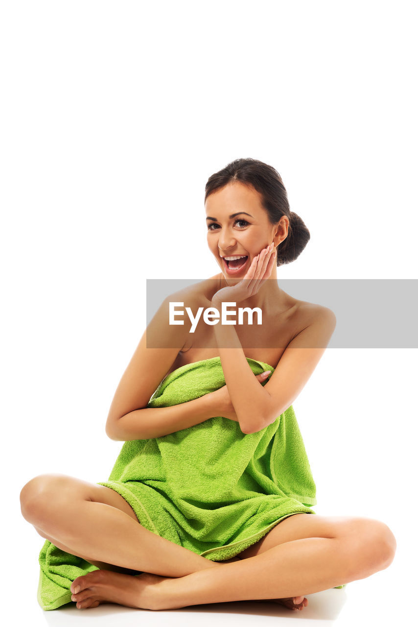 Portrait of cheerful woman green towel sitting against white background
