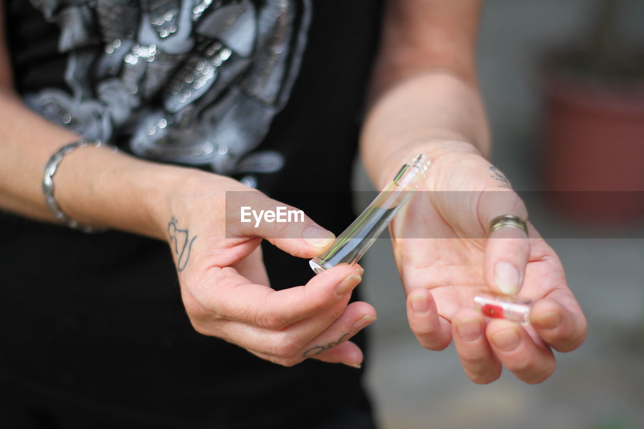 CROPPED IMAGE OF HAND HOLDING CIGARETTE