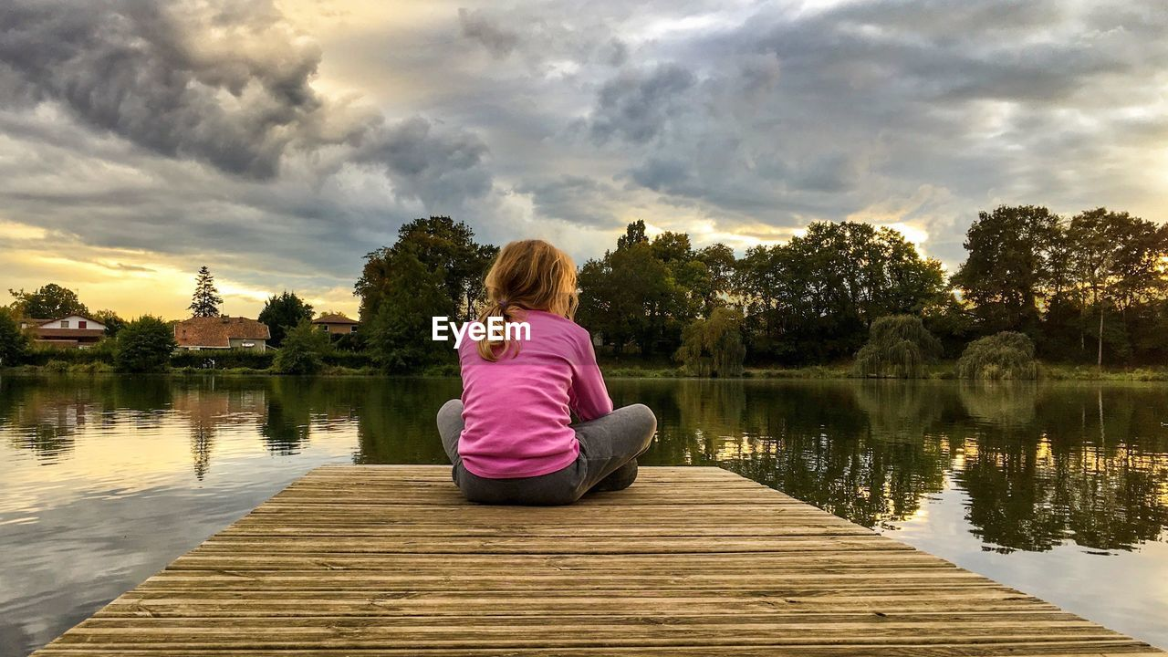 Rear View Of Girl Sitting On Pier Over Lake Against Sky