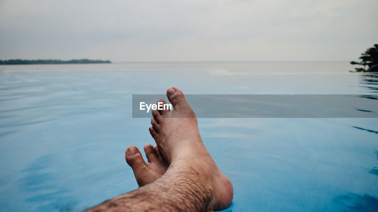 Low section of man relaxing in infinity pool against sea during sunset