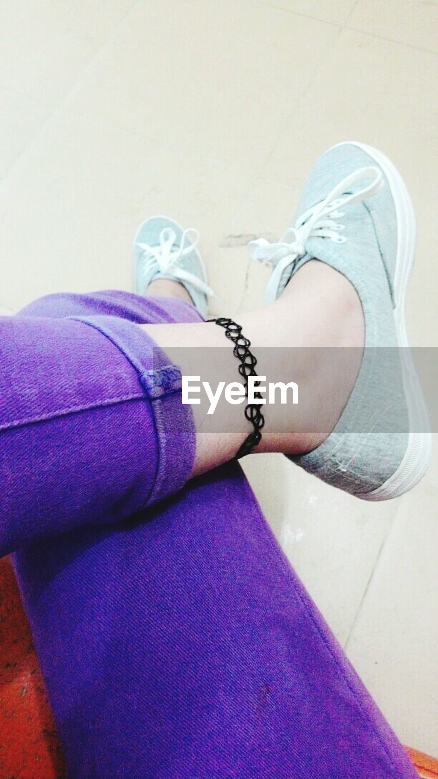 low section, person, shoe, personal perspective, lifestyles, human foot, indoors, jeans, footwear, leisure activity, high angle view, fashion, part of, barefoot, legs crossed at ankle, close-up