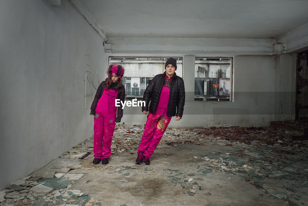 Portrait Of Couple Wearing Warm Clothing While Standing In Abandoned House