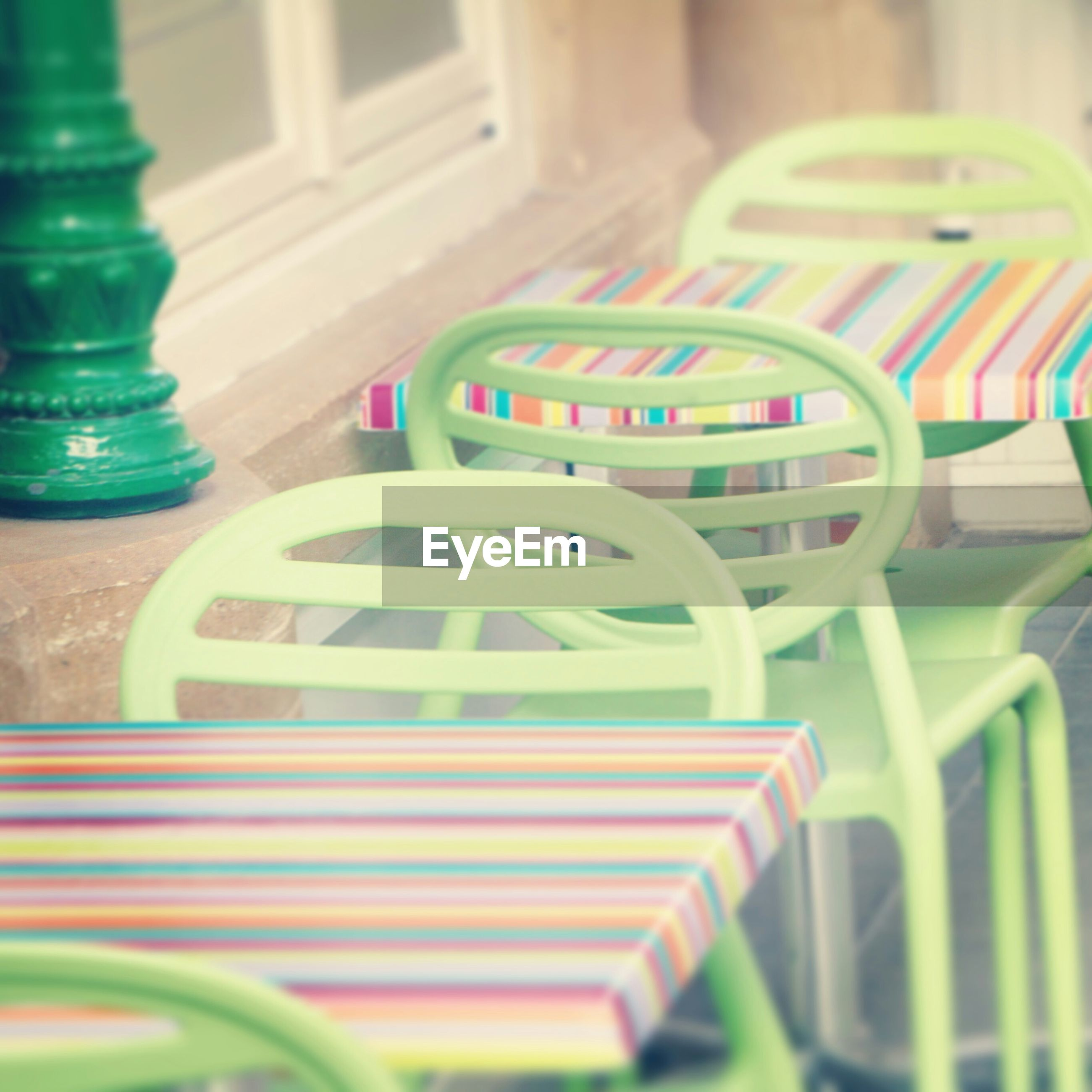 multi colored, empty, chair, absence, indoors, in a row, close-up, green color, no people, selective focus, seat, table, focus on foreground, colorful, pattern, blue, day, still life, built structure, architecture