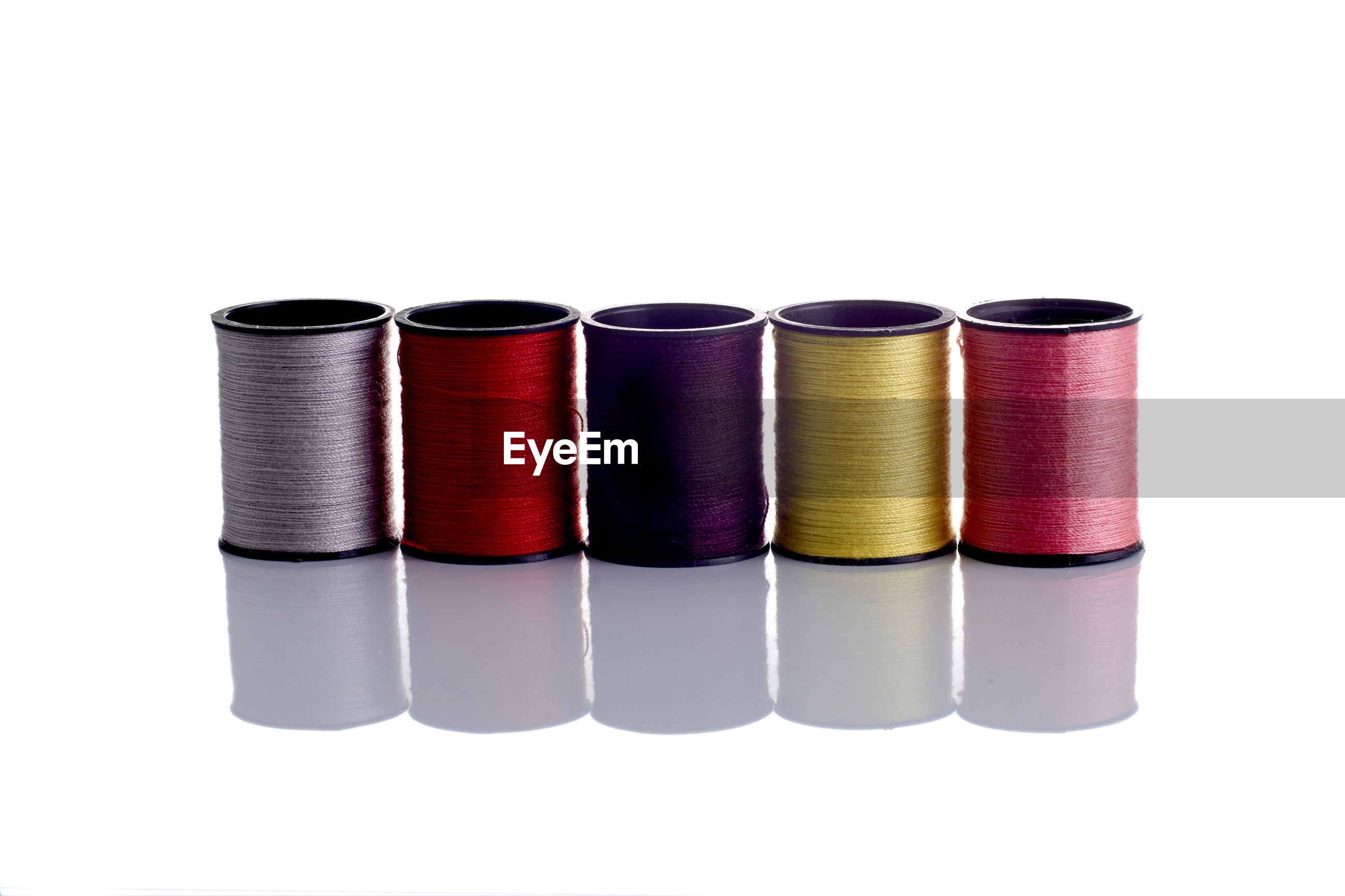 Close-up of colorful spools over white background