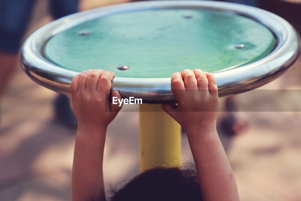 Cropped Image Of Playful Girl Hanging On Outdoor Play Equipment