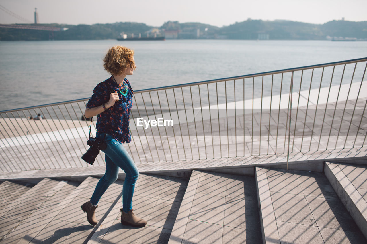 full length, railing, water, leisure activity, lifestyles, one person, real people, casual clothing, nature, day, women, architecture, pier, rear view, sunlight, adult, built structure, sea, hairstyle, outdoors